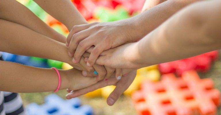 Children's hands joined together in a circle.